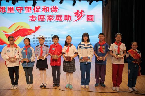 2-与会领导为丰台区中小学生代表颁发《志愿服务户口簿》