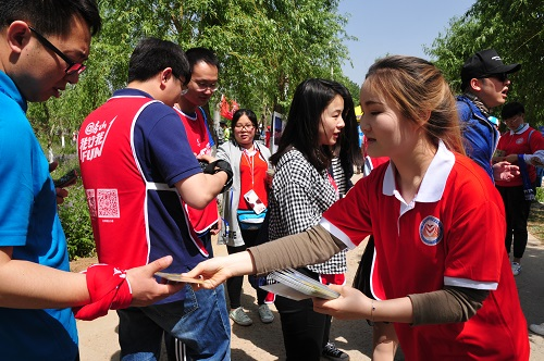 志愿者为参与群众发放沿途认证物
