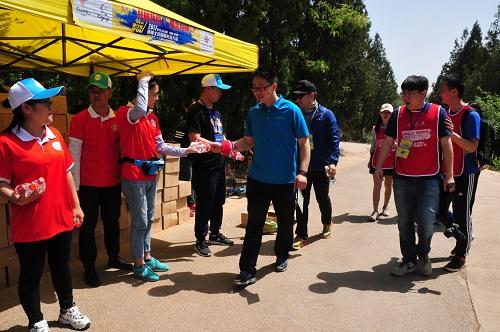 志愿者为参与群众发放饮水