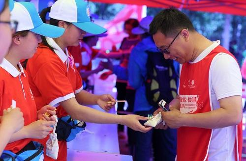志愿者为到达终点的群众发放纪念品