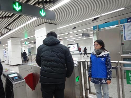 4志愿者引导乘客刷卡