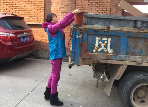 社区志愿者把清理的杂物搬上车