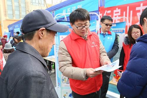 7-志愿者向群众宣传仿假币知识